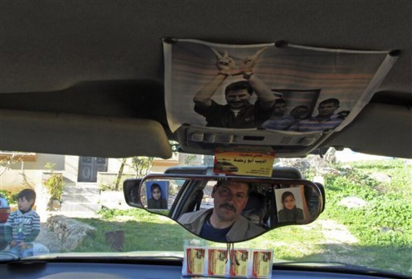 In this Feb. 3, 2013 photo, Palestinian Adib Abu Rahmeh, activist and resident of the West Bank village of Bilin, sits in his taxi where he has pasted a photograph of himself during a court hearing in an Israeli military prison. Dozens of Bilin men and youths were detained and arrested over the pas
