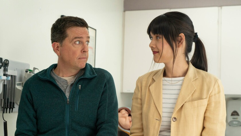 Ed Helms and Patti Harrison look at each other in an exam room.