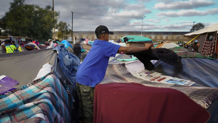 Jose Fajardo from Honduras used old newspapers and spare clothing to help prepare his tent for Wednesday night's forecasted rain. Fajardo is among the thousand of Centro American migrants that have been temporary sheltered at the Benito Juarez Sports Complex in Tijuana, Mexico.