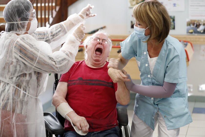 A resident of a nursing home is being tested with a PCR test in Ammerschwihr, eastern France, Monday, Nov.9, 2020. The antigen tests can give results in 15-30 minutes, and if they turn out positive, the patient is sent for a PCR test to confirm the result. (AP Photo/Jean-Francois Badias)