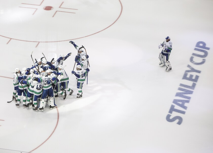 Vancouver Canucks players celebrate a goal against the Minnesota Wild during the third period of an NHL hockey qualifying round game, Friday, Aug. 7, 2020, in Edmonton, Alberta. (Jason Franson/The Canadian Press via AP)