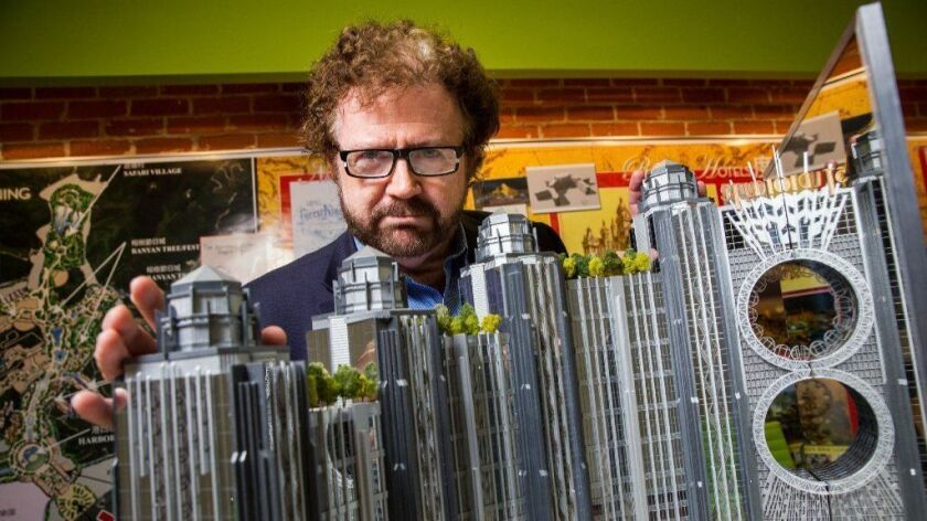 In an October 2015 photo, Goddard is pictured with a model of a Macau casino his firm designed.
