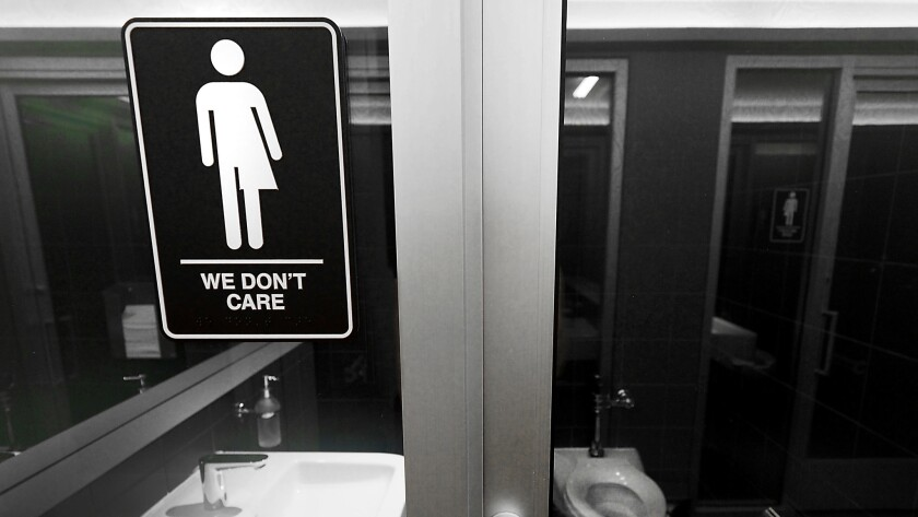 Gender-neutral signs posted in public restrooms in Durham's 21C Museum Hotel.