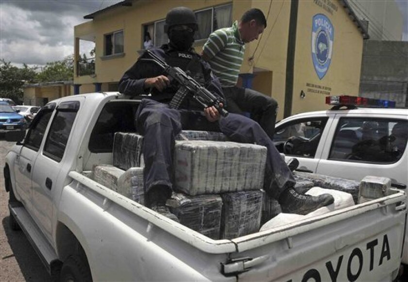 FILE - In this Tuesday July 3, 2012 file photo,  a Honduras national policeman sits on packages of cocaine that were brought to Tegucigalpa, Honduras. The cocaine was seized from a small airplane that crashed after it was being chased by military planes and helicopters of the Honduras army near the