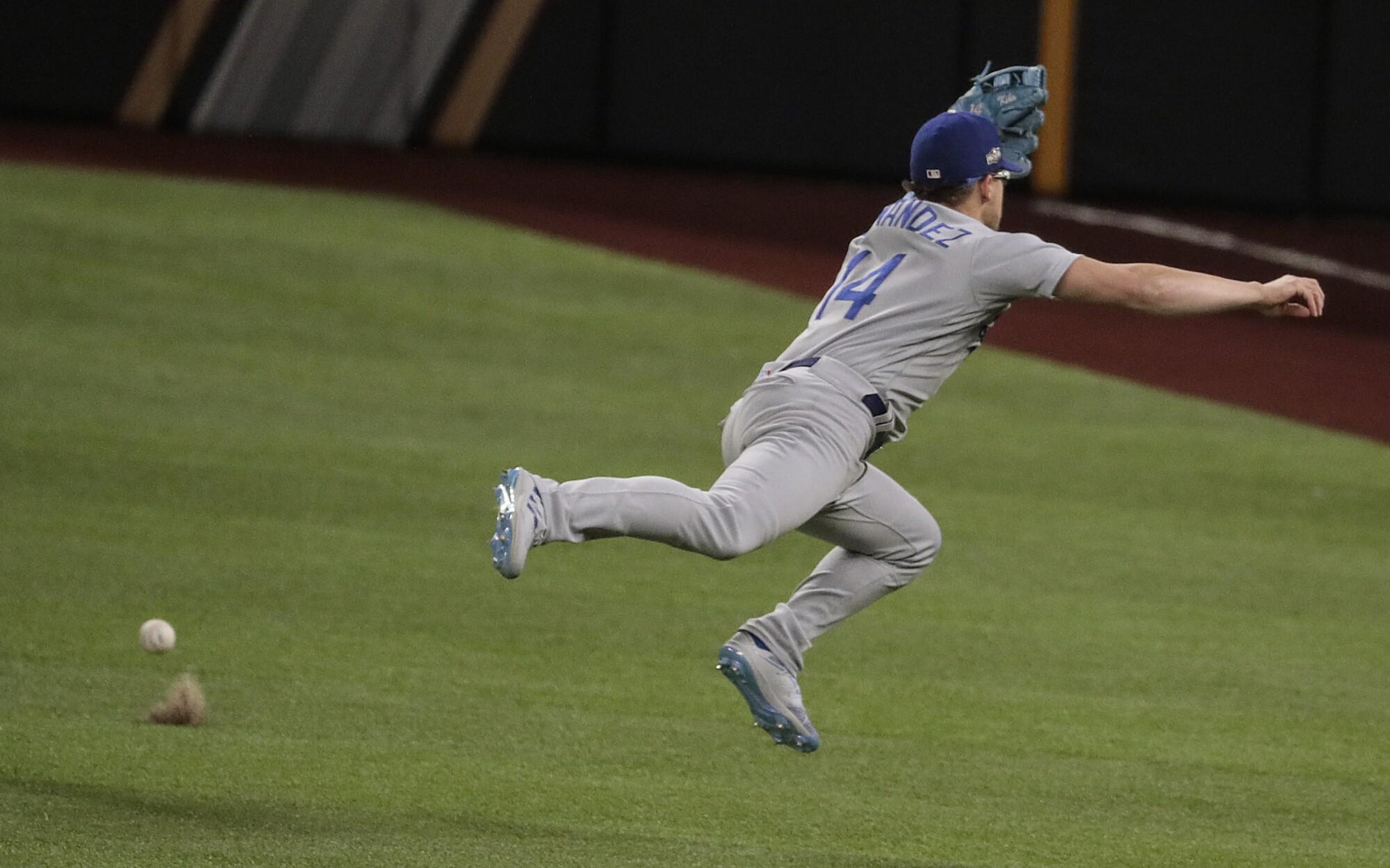 Dodgers second baseman Kiké Hernández can't grab a run-scoring single by Atlanta's Ozzie Albies.