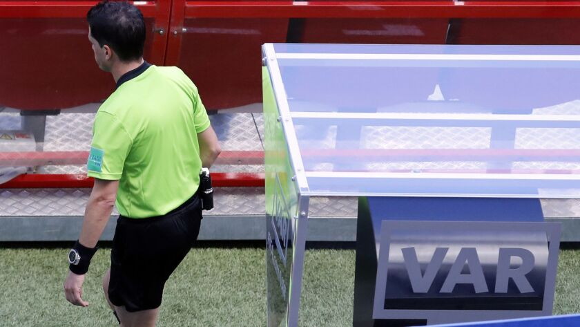 Referee Andres Cunha from Uruguay enter the field after he watches a replay on a screen during the g