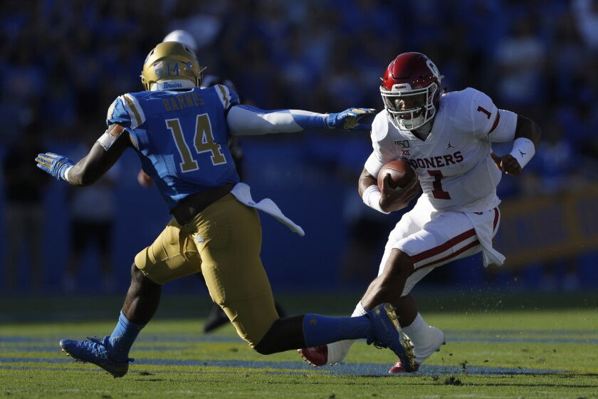 Oklahoma quarterback Jalen Hurts eludes UCLA linebacker Krys Barnes during the first half of the Bruins' 48-14 loss Saturday.