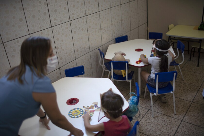 Children wearing face shields as a precaution against the new coronavirus outbreak sit spaced apart in individual tables at the Pereira Agustinho daycare, nursery school and pre-school, after it reopened amid the new coronavirus pandemic in Duque de Caxias, Monday, July 6, 2020. The city of Manaus in the Amazon rainforest and Duque de Caxias in Rio de Janeiro's metropolitan region, became on Monday the first Brazilian cities to resume in-person classes at private schools since the onset of the COVID-19 pandemic, according to the nation's private school federation. (AP Photo/Silvia Izquierdo)