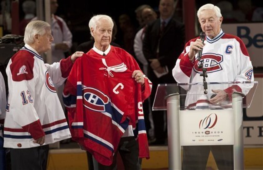 Former Detroit Red Wings' Gordie Howe holds former Montreal Canadiens' Jean Beliveau jersey as Dickie Moore, left,  looks on during centennial celebrations Friday, Dec. 4, 2009 in Montreal. (AP Photo/The Canadian Press, Paul Chiasson)
