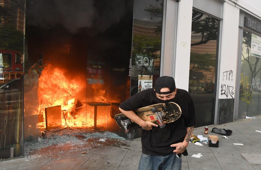 A man runs in front of a burning Sake House restaurant in Santa Monica.