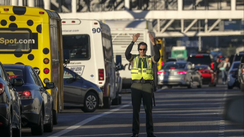 A Los Angeles airport police officer directs traffic at Los Angeles International Airport on Wednesday November 22, 2017.