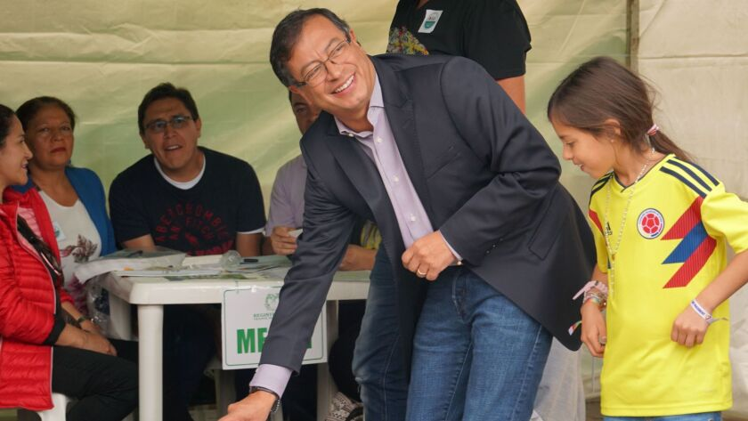 Accompanied by one of his children, Colombian presidential candidate Gustavo Petro votes in Bogota, the capital, on May 27, 2018.