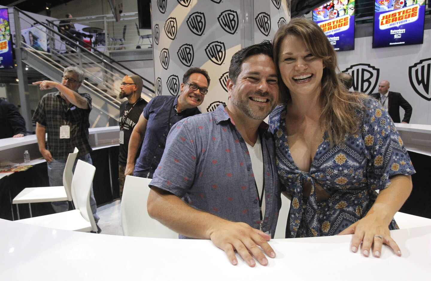 Voice of Wonder Woman Rachel Kimsey and Jason Lewis, voice of Superman, pose for a photo, with Diedrich Bader behind them, after they and other actors with Justice League Action signed autographs at the Warner Brothers booth.