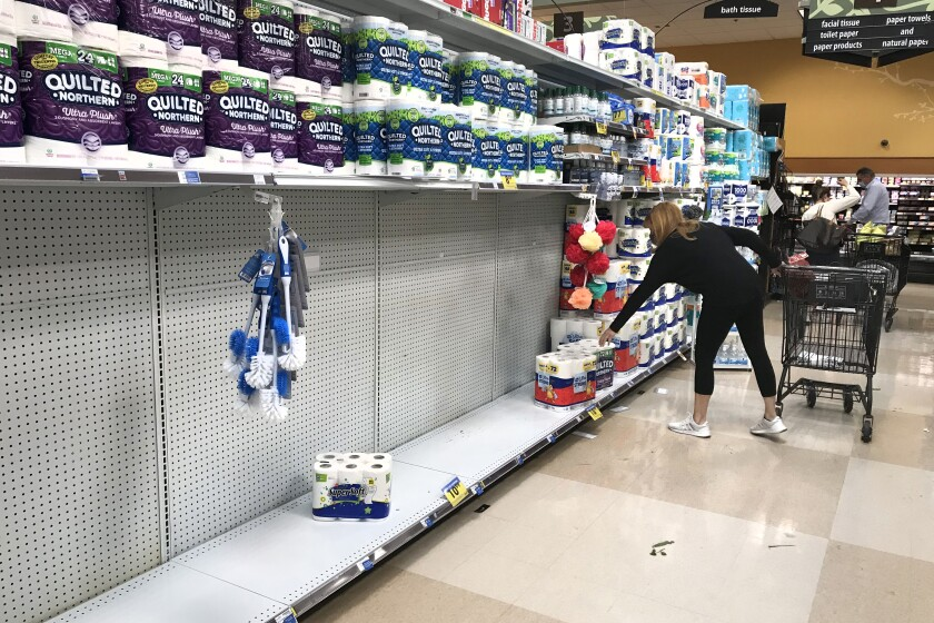 CALABASAS, CA - NOVEMBER 192020: A shopper reaches for a roll of toilet paper on a partially empty shelf at Ralph's market in Calabasas. (Mel Melcon / Los Angeles Times)