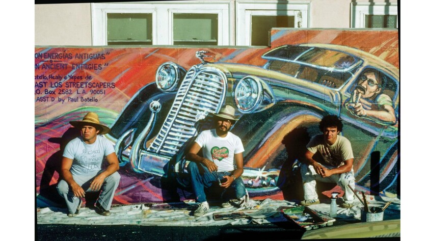 """Wayne Healy, from left, David Botello and George Yepes pose in front of the mural """"Filling Up on Anc"""