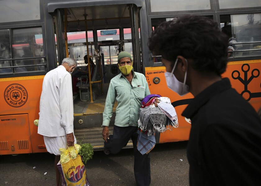 A vendor selling face masks disembarks a bus as he looks for prospective buyers at a bus station in Bengaluru, India, Tuesday, Jan. 5, 2021. India authorized two COVID-19 vaccines on Sunday, paving the way for a huge inoculation program to stem the coronavirus pandemic in the world's second most populous country. (AP Photo/Aijaz Rahi)