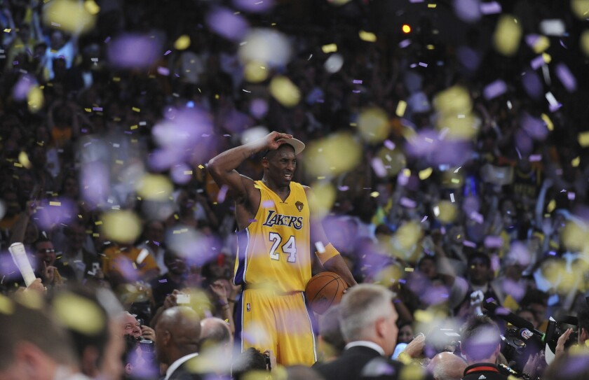 Kobe Bryant celebrates on the scorer's table at Staples Center after the Lakers defeated the Celtics to win the NBA championship on June 17, 2010.