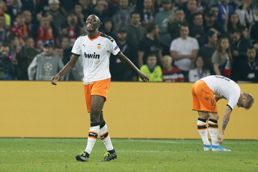 """FILE - In this Oct. 23, 2019, file photo, Valencia's Mouctar Diakhaby, left, leaves the pitch after receiving a red card during the group H Champions League soccer match between Lille and Valencia at the Stade Pierre Mauroy - Villeneuve d'Ascq stadium in Lille, France. Valencia stopped playing its Spanish league game at Cadiz on Sunday, April 4, 2021 and walked off the field after one of its players said he was racially insulted by an opponent. The club said it resumed the game after feeling threatened by the referee with the loss of points. Valencia left the field after Diakhaby said he was insulted by Cadiz defender Juan Cala, who denied any wrongdoing. Cadiz, from southern Spain, condemned racism but said it """"cannot comment on incidents that arise between players during the course of play."""" (AP Photo/Michel Spingler, File)"""