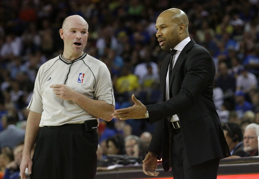 New York Knicks coach Derek Fisher, right, talks with referee Gary Zielinski during the first half of an NBA basketball game against the Golden State Warriors in Oakland, Calif., Saturday, March 14, 2015. (AP Photo/Jeff Chiu)