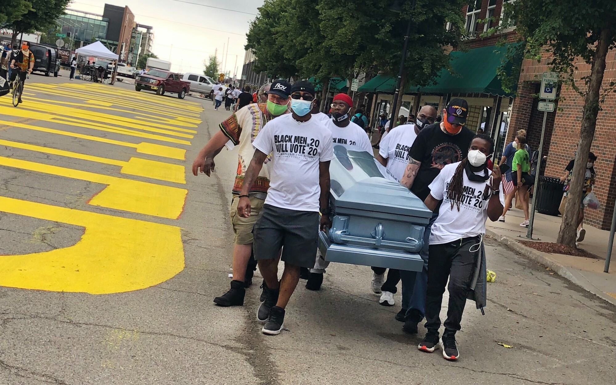 Volunteers carry an empty coffin past a new Black Lives Matter in Tulsa, Okla., for Juneteenth.