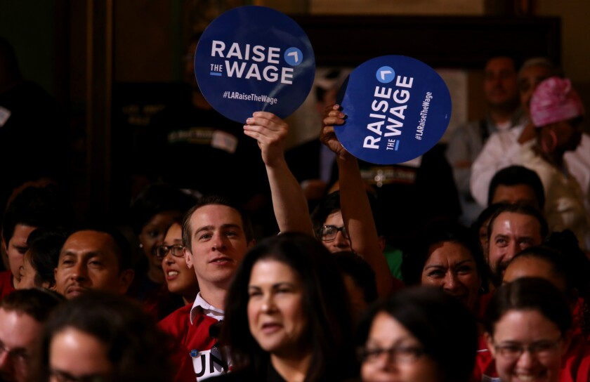 Members of Unite Here show their support for raising the minimum wage before the Los Angeles City Council vote.