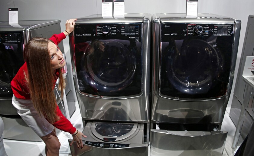 An employee shows washers and dryers that can be controlled via a smartphone app at the International Consumer Electronics Show in Las Vegas on Jan. 6, 2015.