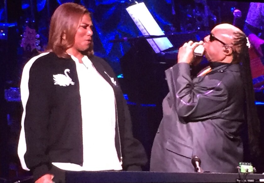 Queen Latifah marvels at Stevie Wonder's harmonica solo during one of her numbers at Wonder's 20th anniversary House Full of Toys benefit concert Friday, Dec. 9, at the Microsoft Theatre in Los Angeles