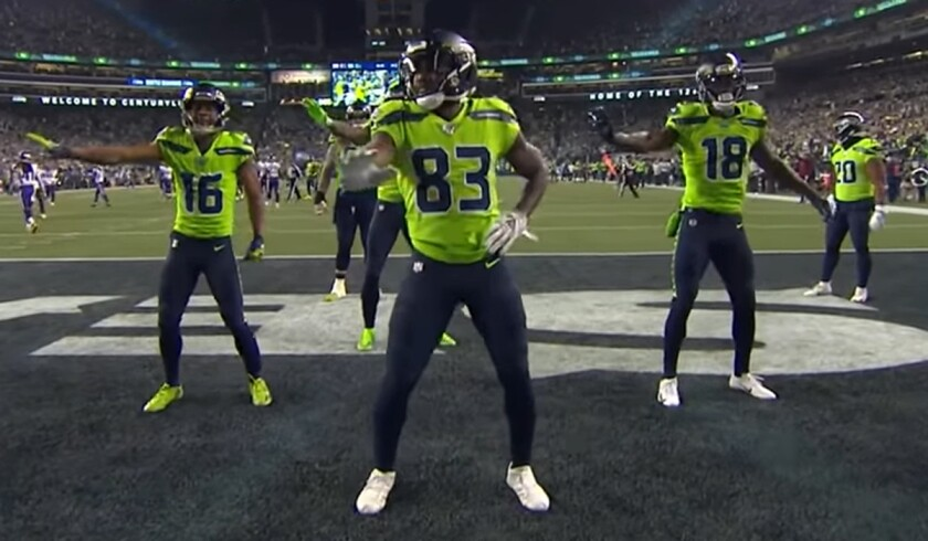 Seattle Seahawks receivers Tyler Lockett (16), David Morre (83) and Jaron Brown (18) celebrate a touchdown with New Edition dance moves.