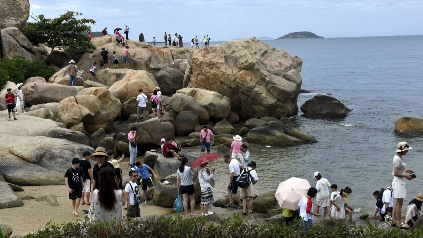 --FILE--Tourists, most of whom are from China, visit the Truong Son Mountains in Nha Trang, Khanh Ho