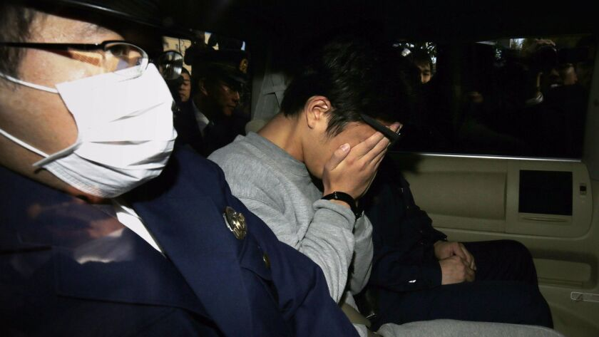 Takahiro Shiraishi covers his face as he is transported to a prosecutor's office from a police station in Tokyo on Nov. 1. Shiraishi was arrested after police found nine dismembered corpses rotting in his apartment.
