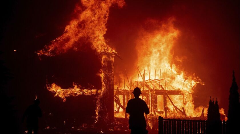 FILE - In this Thursday, Nov. 8, 2018 file photo, a home burns as the Camp Fire rages through Paradi