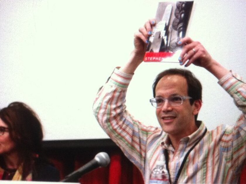 """Poet Stephen Burt holds up his book """"Parallel Play"""" before reading one of his poems aloud during the L.A. Times Festival of Books."""
