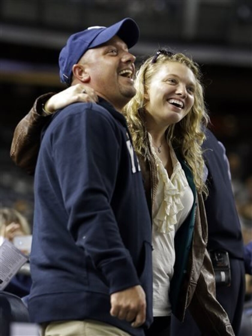 "Two fans embrace while singing ""Sweet Caroline"" as a tribute to the victims of the Boston Marathon explosions after the third inning of a baseball game between the New York Yankees and the Arizona Diamondbacks at Yankee Stadium in New York, Tuesday, April 16, 2013. The song by Neil Diamond has been a longtime fixture as a fan sing-along during the bottom of the eighth inning of Boston Red Sox games. In big ways and small, New York is putting aside its heated and historical rivalry with Boston in"