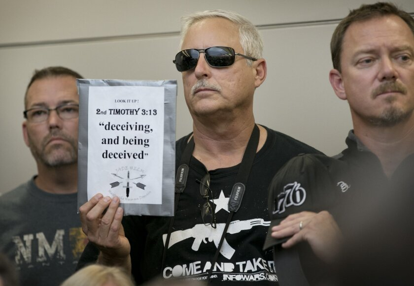 Bob Welch holds a sign at a public hearing about the Jade Helm 15 military training exercise in Bastrop, Texas.