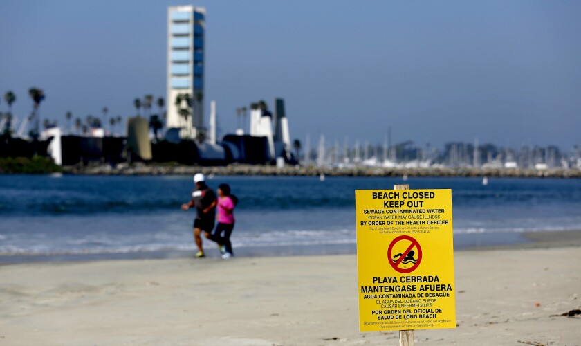 Two people jog along the shoreline in Long Beach on July 19, after officials closed the beach to swimming following a sewage spill.