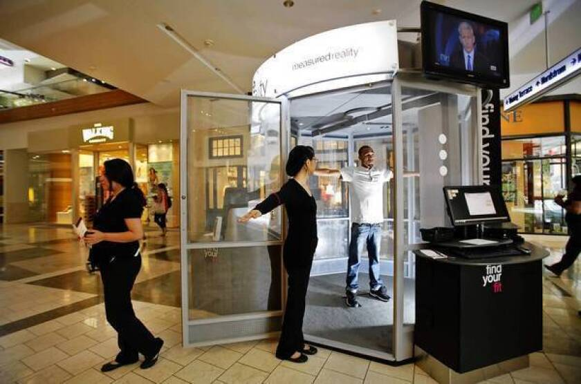 Sandra Garcia, left, the station manager at the Me-Ality sizing machine in the Westfield Topanga mall, helps Quincy Thomas, 19, get into position before the machine scans him.