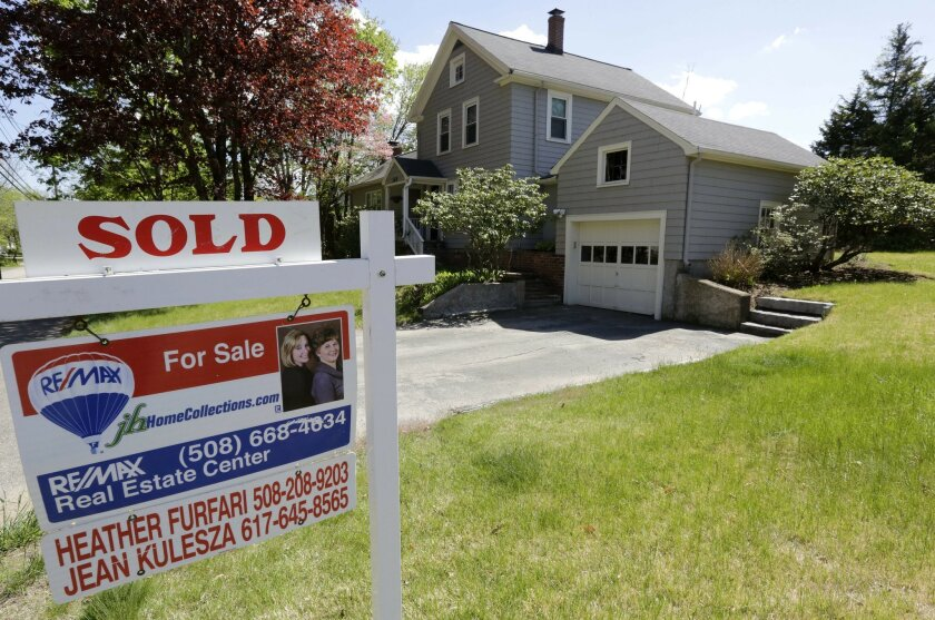 """This Wednesday, May 18, 2016, photo shows a """"Sold"""" sign in front of a house in Walpole, Mass. On Friday, May 20, the National Association of Realtors reports on sales of existing homes in April. (AP Photo/Steven Senne)"""