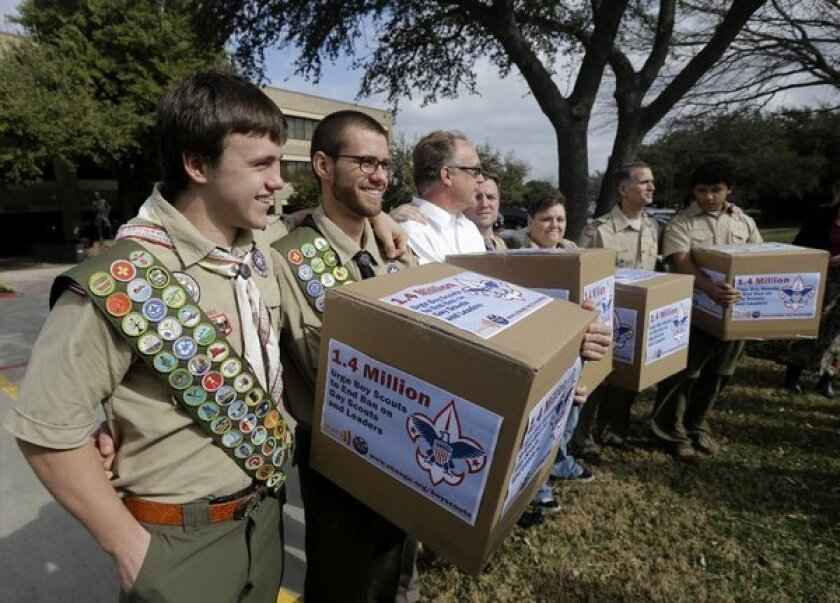 James Oliver, left, hugs his brother and fellow Eagle Scout, Will Oliver, who is gay, as Will and other supporters carry four boxes filled with a petition in front of the Boy Scouts of America headquarters in Dallas. Boy Scout officials are surveying adult members about their attitudes on gay membership, which will be voted on in late spring.