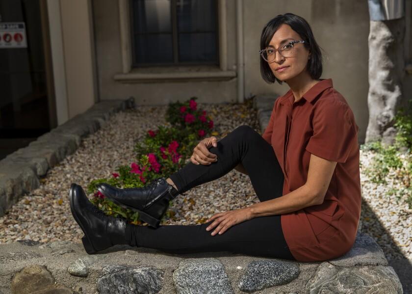 Carribean Fragoza se asienta sobre un muro de piedra en los terrenos de la Universidad de Graduados de Claremont.