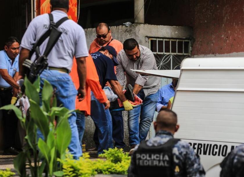 """Vista de varios peritos forenses realizando el levantamiento de un cadáver. La UE expresó también su """"preocupación por la falta de resultados en las investigaciones abiertas para esclarecer casos anteriores de asesinatos de periodistas en México"""". EFE/Archivo"""