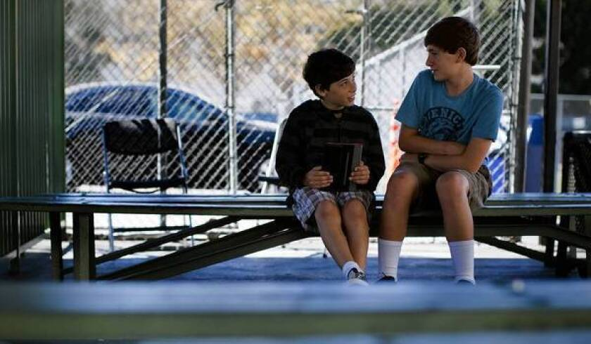 Daniel Furth,11, left, and his brother Eric, 15, chat on playground benches after Jewish Sunday School. The school teaches children about Jewish history, culture and values.