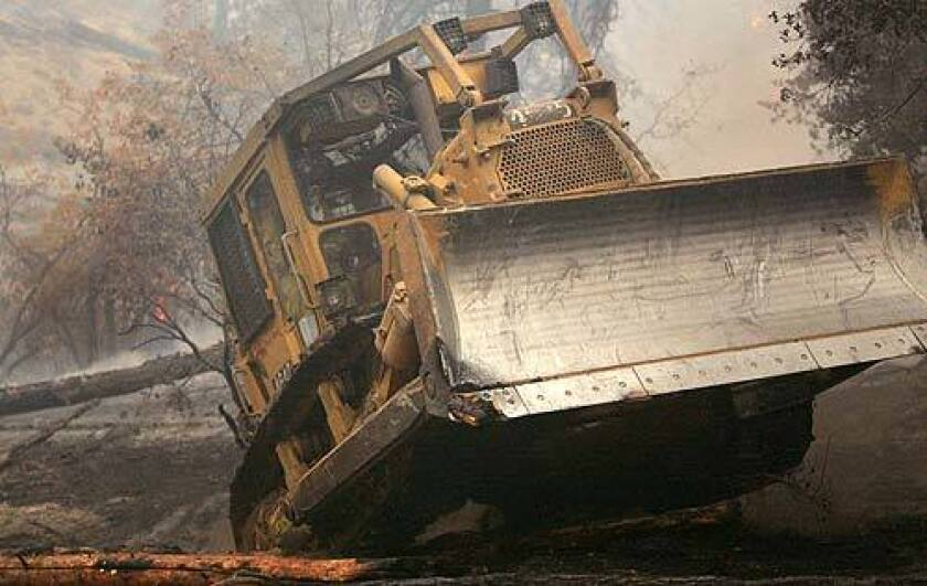 Bulldozer operator Chris Ivey makes his way over a log near Arrowbear in an attempt to keep fire from jumping California 18.