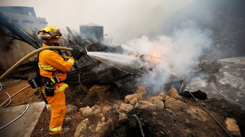 Firefighter Chris Black with the Sacramento Fire Department douses flames Tuesday in Toro Canyon in Carpinteria.