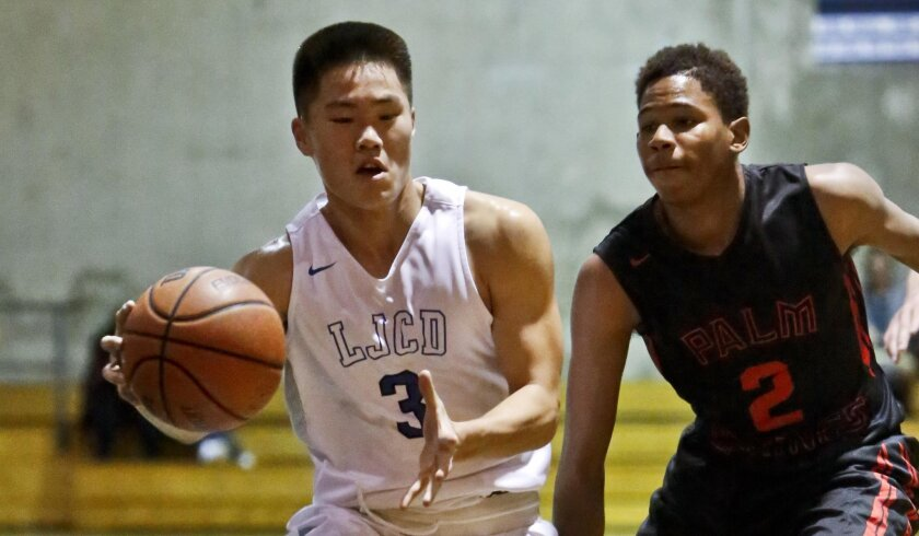 La Jolla Country Day sophomore Alex Cho drives to the basket against Palm Springs' Deondre Hawkins. Cho is among three sophomores and five freshmen on a Torreys team that stands 15-0.