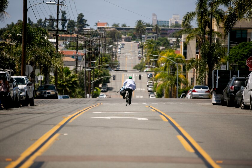 "A man on a bicycle rides down Howard Street, which has been designated a ""slow street,"" meaning it's shut off to thru traffic to make room for cyclists and pedestrians to socially distance, on May 4, 2020 in San Diego, California."