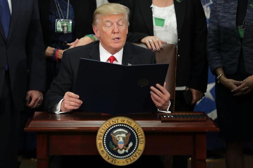 El presidente estadounidense, Donald J. Trump (c), lee la firma de la orden ejecutiva para destinar fondos federales a la construcción del muro con México durante una ceremonia en el Departamento de Seguridad Nacional en Washington, Estados Unidos, hoy 25 de enero de 2017. EFE/POOL/ PROHIBIDO SU USO POR AFP