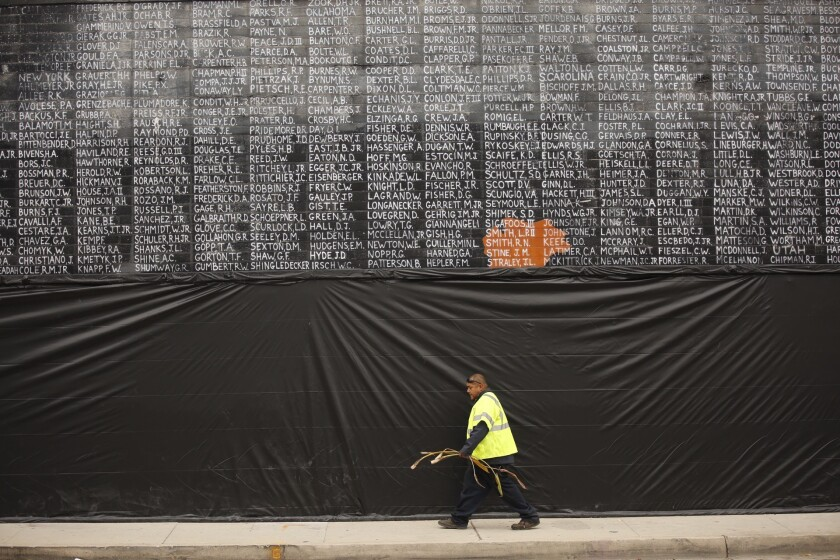 A man walks past the Vietnam veterans mural, which was covered with plastic after it was vandalized just before Memorial Day.