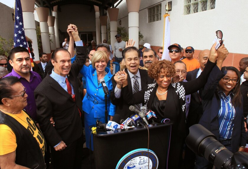 Carson Mayor Jim Dear, left, with Congresswoman Janice Hahn raise their hands with other Carson civic and labor leaders cheer the effort to bring a shared Chargers/Raiders stadium to their city.
