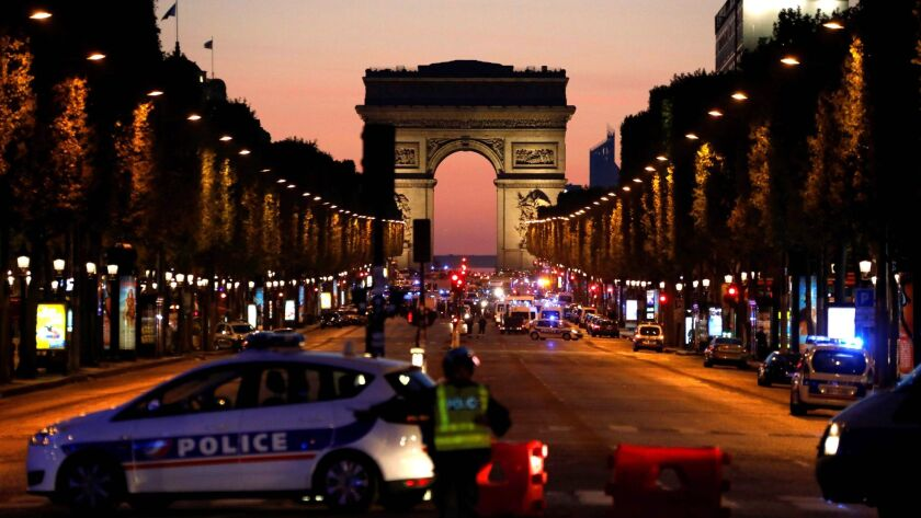Police officers block the access to the Champs Elysees in Paris after a shooting.