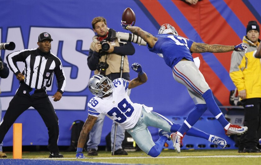 FILE - In this Nov. 23, 2014, file photo New York Giants wide receiver Odell Beckham Jr. (13) makes a one-handed catch for a touchdown against Dallas Cowboys cornerback Brandon Carr (39) in the second quarter of an NFL football game in East Rutherford, N.J. Beckham grabbed The Associated Press NFL